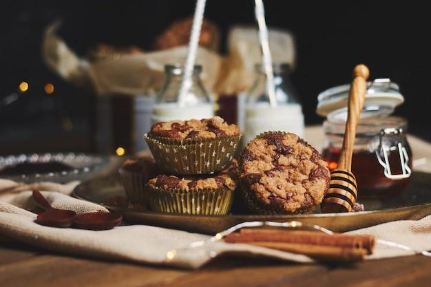 Messa a fuoco selettiva di deliziosi muffin di biscotti di natale su un piatto con miele e latte