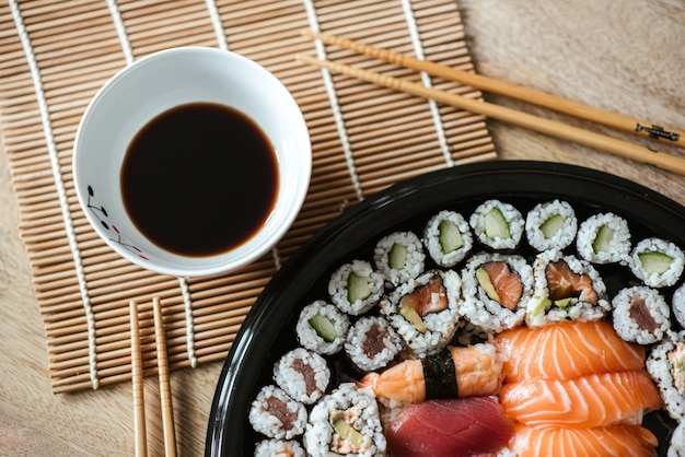 Selective focus shot of the delicious sushi rolls served in a black round plate Free Photo