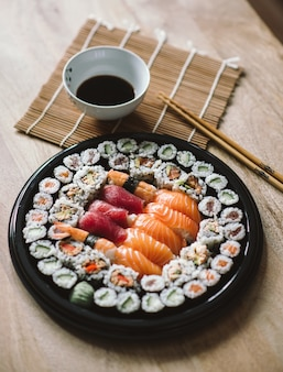 Selective focus shot of the delicious sushi rolls served in a black round plate
