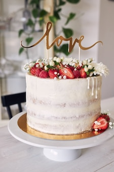 Selective focus shot of delicious white wedding cake with red berries, flowers and cake topper