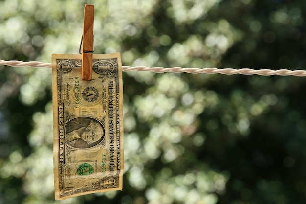 Selective focus shot of a dollar bill hung from a wire with a clothespin
