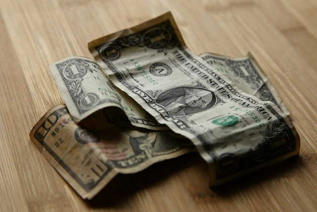 Selective focus shot of dollar bills on top of each other on a wooden surface