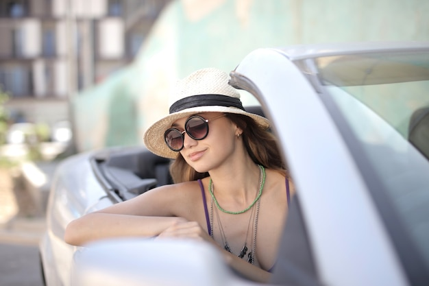 Selective focus shot of female on the driver seat of a white convertible sports car