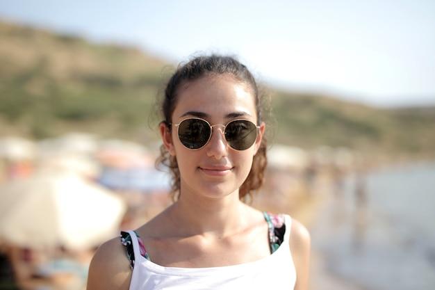 Colpo di messa a fuoco selettiva di una donna con gli occhiali in spiaggia
