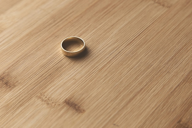 Selective focus shot of a golden wedding ring on a wooden surface