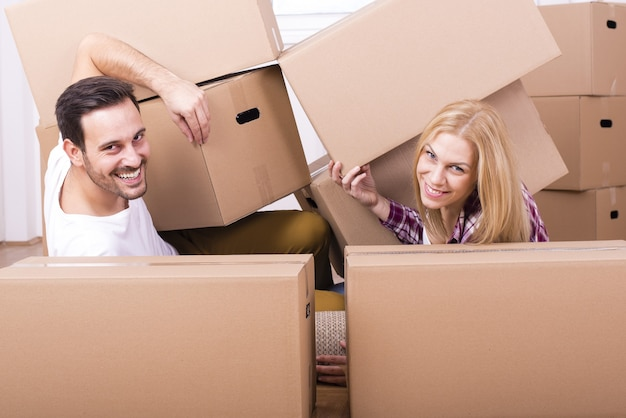 Selective focus shot of a happy white couple moving in together into a new house