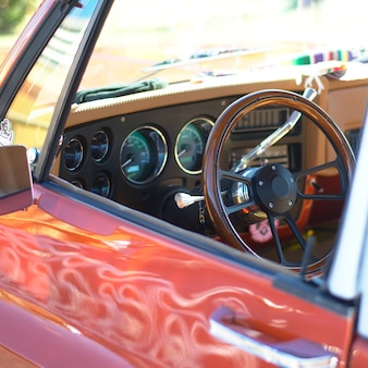 A selective focus shot of a low rider car steering wheel