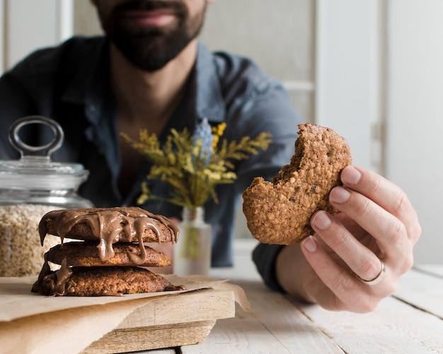 Colpo di messa a fuoco selettiva di un maschio di mangiare deliziosi biscotti al cioccolato