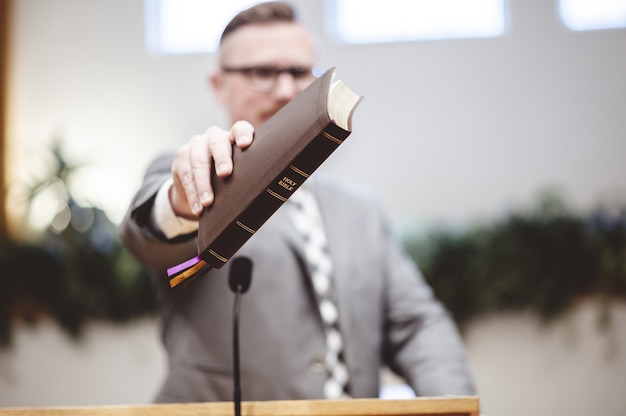 Selective focus shot of a male standing and holding a book in hands