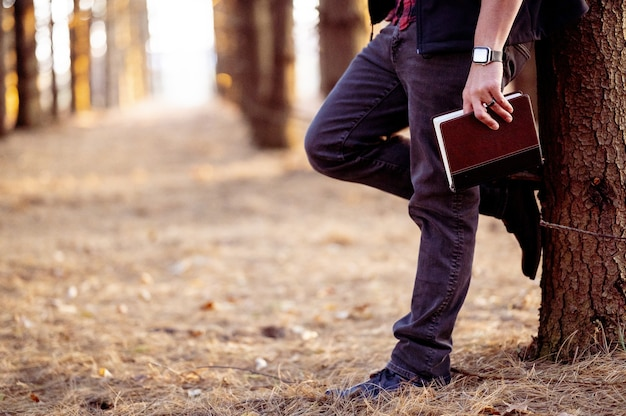 Selective focus shot of a man holding a book posing in a forest