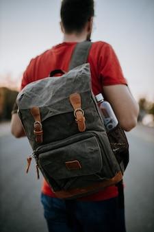 フラップバックパックと水筒を持って道路に立っている選択的なフォーカスショットの男。