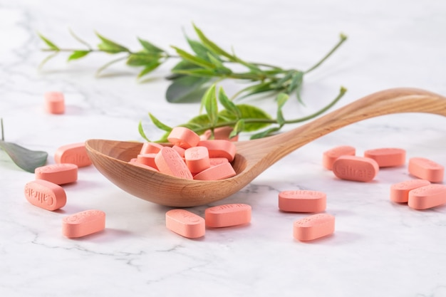 Selective focus shot of medical pills on a wooden spoon with green leaves