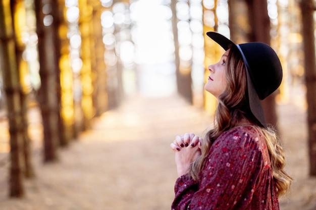 森の中で祈る美しい若い女性の選択的なフォーカスショット