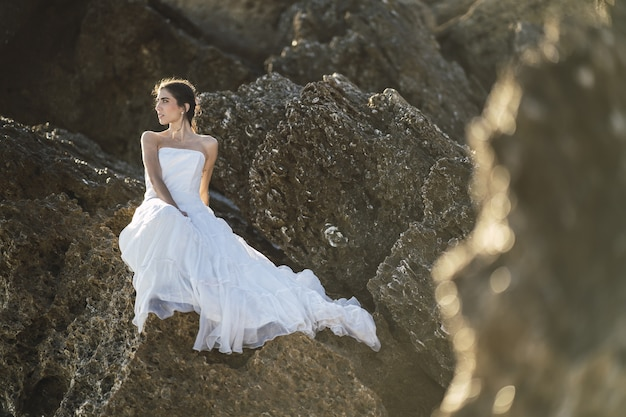 Селективный снимок брюнетки в белом платье, позирующей на скалах