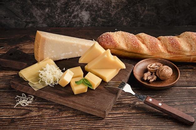 クルミとパンを載せたテーブルの上のおいしいチーズの盛り合わせのセレクティブフォーカスショット