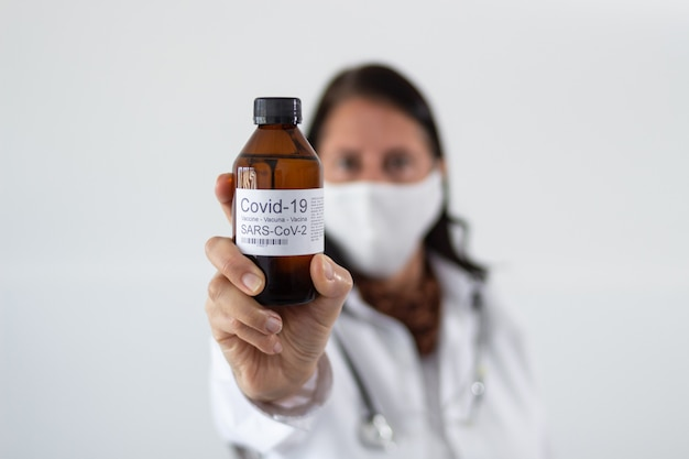 コロナウイルスのワクチンのボトルを保持している女性医師の選択的なフォーカスショット