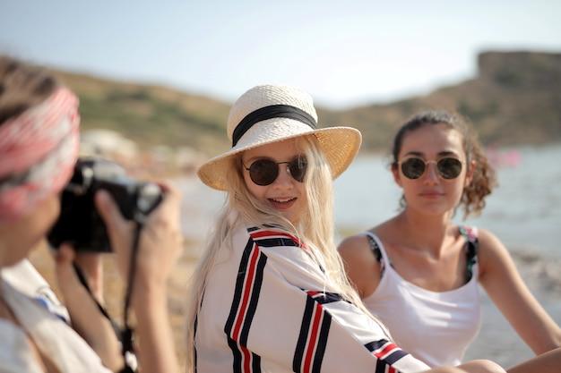 彼女の2人の親友の写真を撮る女性の選択的なフォーカスショット