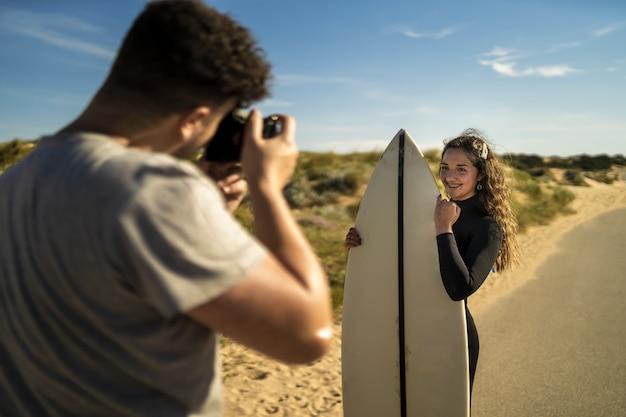 サーフボードを持っている魅力的な女性の写真を撮る写真家の選択的なフォーカスショット