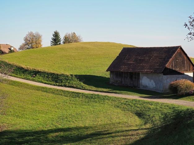 화창한 날에 언덕에 시골 집과 나무의 선택적 초점 샷