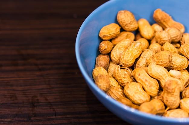 ピーナッツの鮮やかな青いボウルの選択的なフォーカスショット