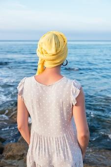 Селективный фокус снимок молодой женщины, расслабляющейся на берегу моря