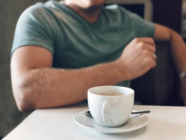 コーヒーを飲む若い男性の選択的なフォーカスショット