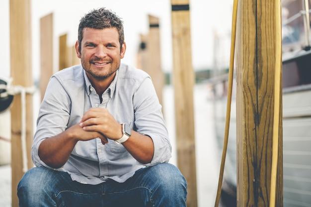 Селективный фокус выстрел молодого улыбающегося мужчины, сидящего в гавани
