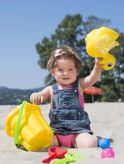 해변에서 노는 사랑스러운 어린 소녀의 선택적 초점 샷