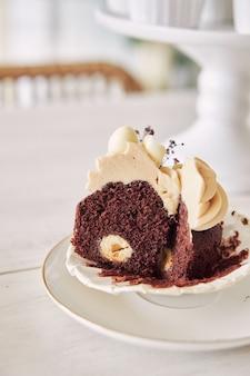 흰색 크림 토핑이 있는 맛있는 초콜릿 컵케이크의 선택적 초점 샷