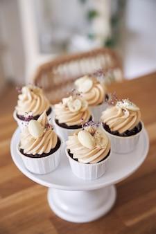 ホワイトクリームをトッピングした美味しいチョコレートカップケーキのセレクティブフォーカスショット