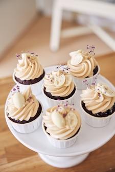흰색 크림 토핑을 곁들인 맛있는 초콜릿 컵케이크의 선택적 초점 샷