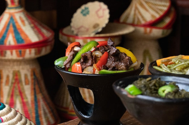 Селективный снимок вкусной эфиопской кухни со свежими овощами на деревянном столе