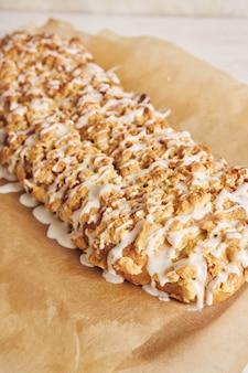 하얀 탁자에 흰 설탕 유약을 넣은 맛있는 양귀비 씨앗 케이크의 선택적 초점