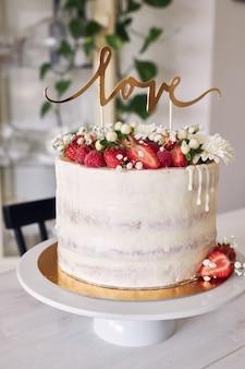 Селективный снимок восхитительного белого свадебного торта с красными ягодами, цветами и топпером для торта