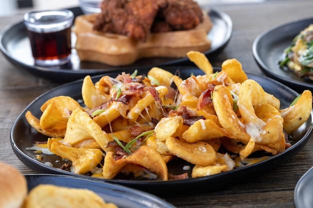 나무 테이블에 녹인 치즈와 얇게 썬 소시지를 곁들인 감자튀김의 선택적 초점