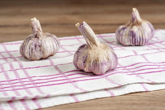 Селективный снимок головок чеснока на полотенце на деревянном столе