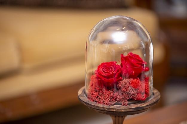 ガラスの地球儀の装飾的な小さな赤いバラの選択的なフォーカスショット
