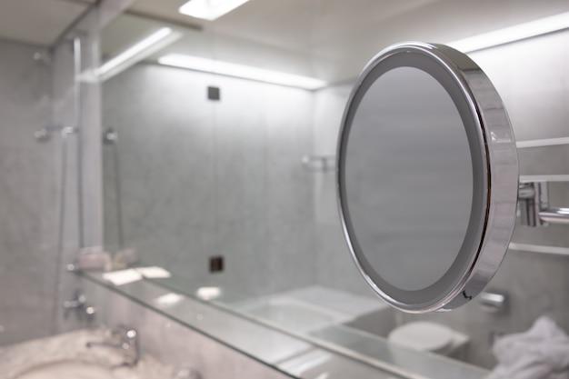 흰색 인테리어가있는 욕실 거울의 선택적 초점 샷