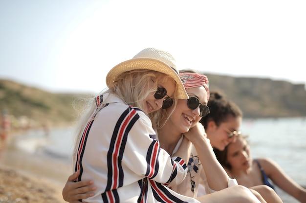 두 젊은 여성의 선택적 초점 샷은 해변에 앉아 서로 포옹