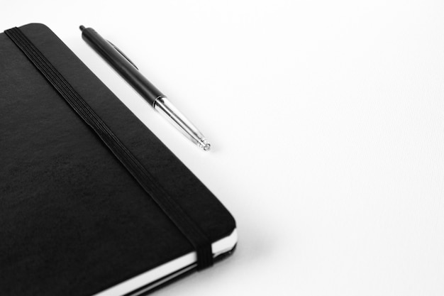 Selective focus shot of a pen near a notebook on a white surface