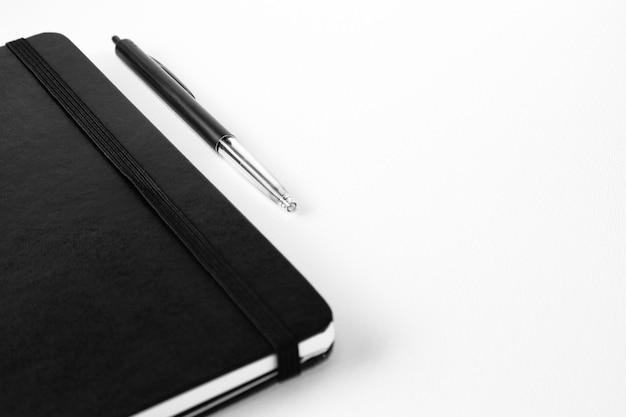 Colpo di messa a fuoco selettiva di una penna vicino a un taccuino su una superficie bianca
