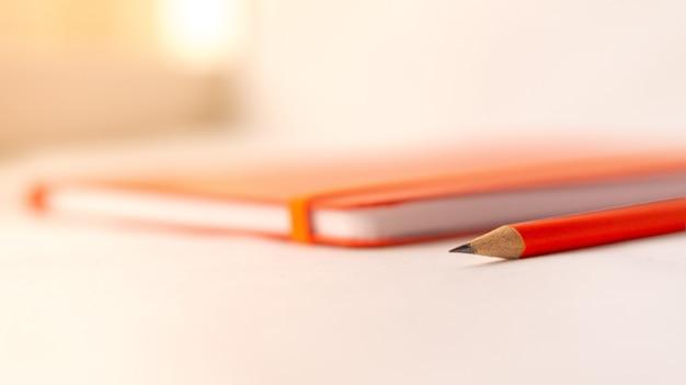 Messa a fuoco selettiva di una matita e un taccuino su un tavolo bianco