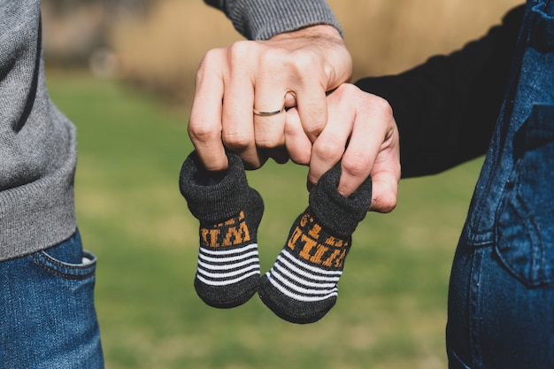 Selective focus shot of a pregnant female and her husband holding small shoes in hands