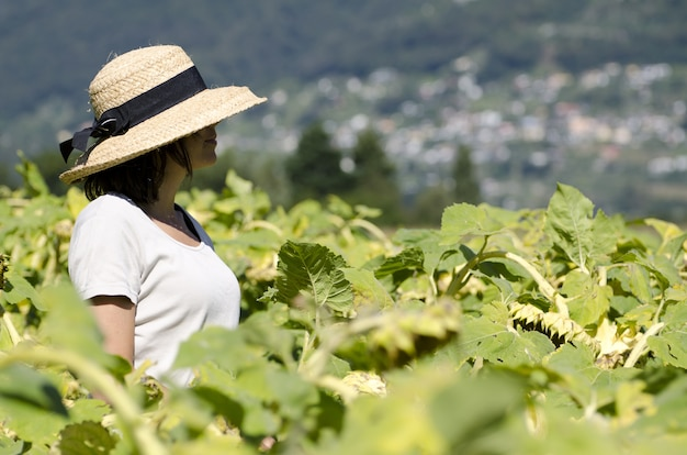 Selective focus shot of pretty female with hat and white shirt standing in a green plant field