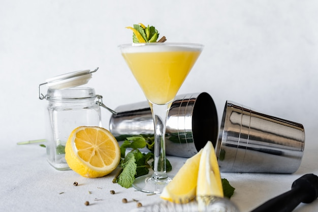 Selective focus shot of a refreshing drink decorated with lemon peel and mint leaves