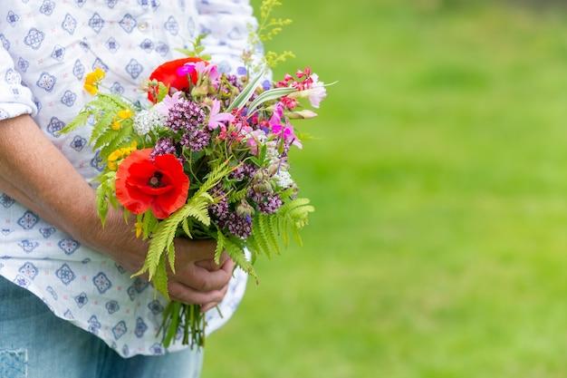 Colpo di messa a fuoco selettiva di qualcuno che tiene un mazzo di fiori diversi all'aperto durante la luce del giorno