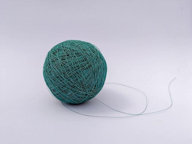 Selective focus shot of a turquoise thread yarn isolated in a white background
