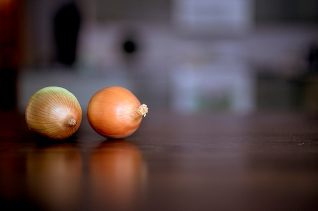 A selective focus shot of two onions on a wooden surface