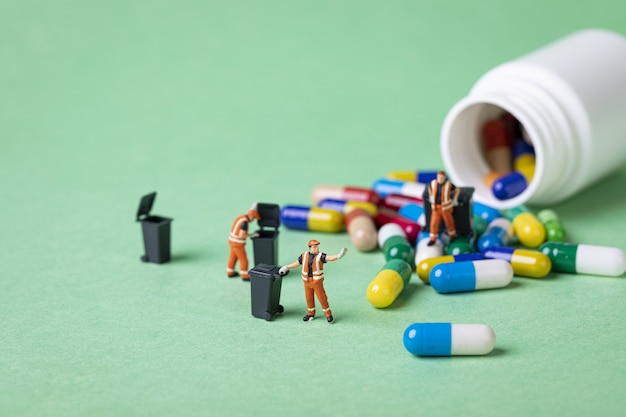 Selective focus shot of waste collector toys and capsules - medicine preservation concept
