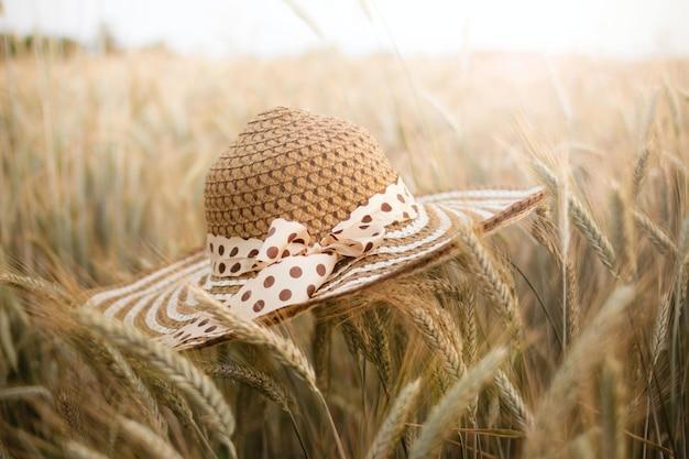Colpo di messa a fuoco selettiva di un campo di grano con un cappello di paglia in primo piano